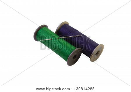 macro threads green and blue color on reels with an iron needle isolate on a white background