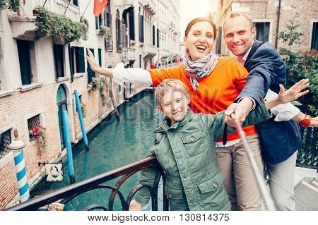 Happy family take a self photo on the one of bridges in Venice