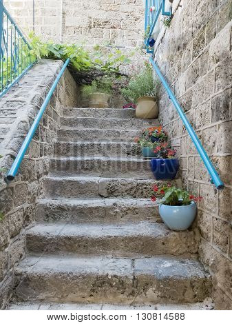 Stone stairs with flowers in front of house entrance. Detail of the facade of home in Jaffa Israel.