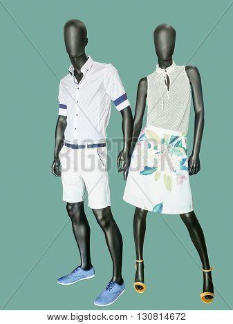 Two mannequins male and female dressed in summer clothes. Isolated on green background. No brand names or copyright objects.