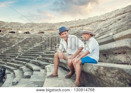 Father and sitting together on antique ruins amphitheater. Side Turkey