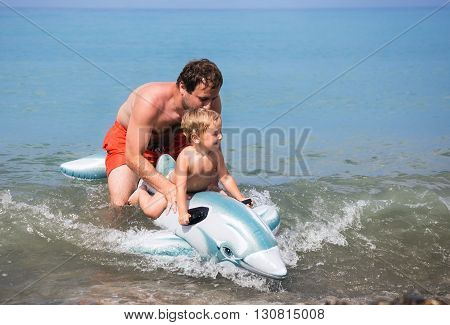 Cheerful father and son swimming in the sea on an inflatable toy dolphin