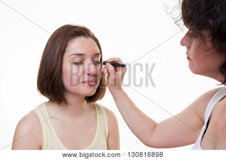 Make-up artist applying liquid eyeliner with brush close up