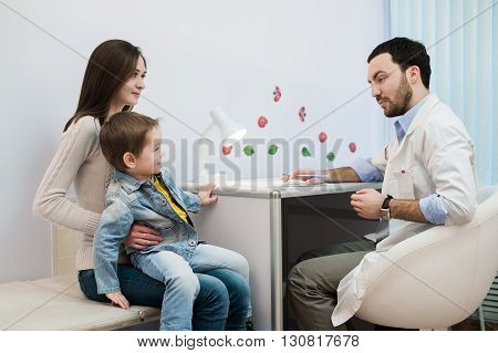 Pediatrician talking to mother and child at hospital