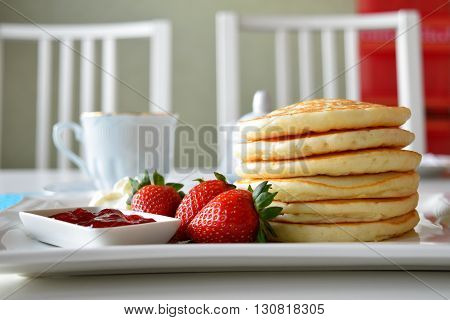 Pancakes served with fresh strawberry, strawberry jam and whipped cream.