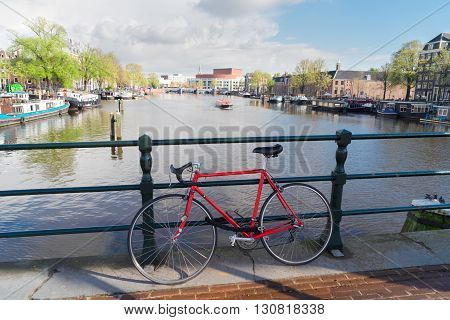 Old bicycle standing next to Amstel canal in Amsterdam, Netherlands