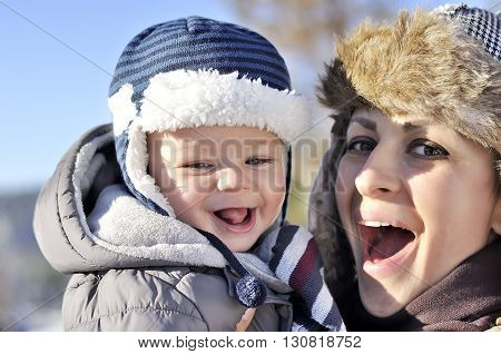 Happy Family. Young Mother In A Winter Park With Her Sweet Baby Boy
