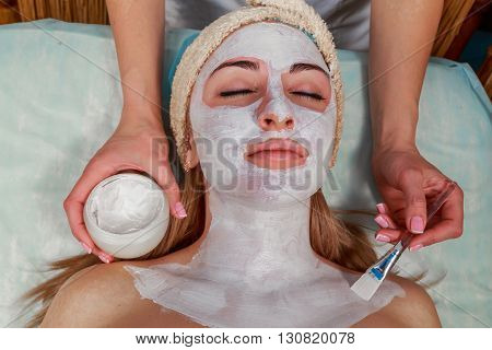 Girl with a beautician at spa salon. Beautician performs cosmetic procedures.applying cosmetic cream. Cosmetology facial beauty - The concept of facial skin care. Article about cosmetology.