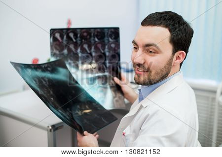 hospital doctor holding patient's x-ray film and mri, looking away and smiling.