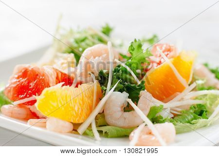 Fresh yummy shrimp salad with oranges and grapefruit  and cheese on the white dish. Close up. Top view of seafood salad with shrimp