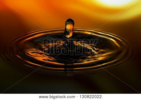 Close-up of water drop on orange yellow background