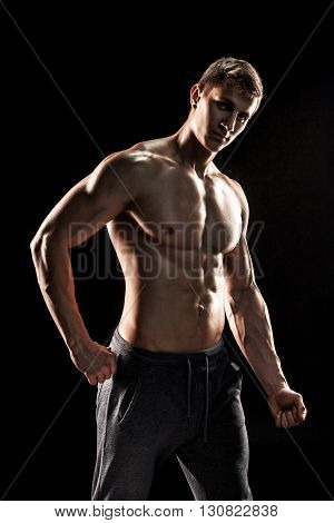 Strong bodybuilder man posing with perfect abs, houlders, biceps, triceps and chest on black background.
