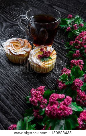 Black tea and muffins on a wooden background