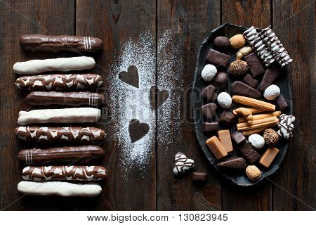 Chocolate candies set flat lay on dark wooden table background. Bunch of candies on black dish. Table decorated with sugar powdered hearts top view