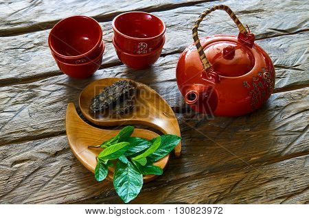 Dried tea and teapot with mint in wooden dish on the table