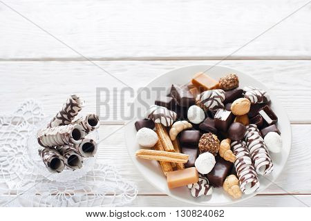 Sweets, chocolate candies, cookies on plate and chocolate sticks in vase on white wooden table top view. Vase on white lace napkin flat lay with copyspace. Chocolate candies set
