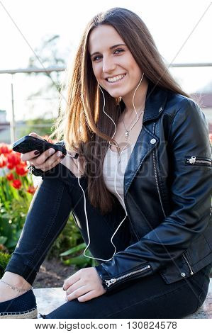 Young woman in the headphones is sitting on the stone parapet holding a smartphone in the hands and smiling