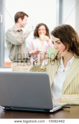 Team of young successful businesspeople talking and drinking coffee at office, businesswoman working on laptop computer in front.