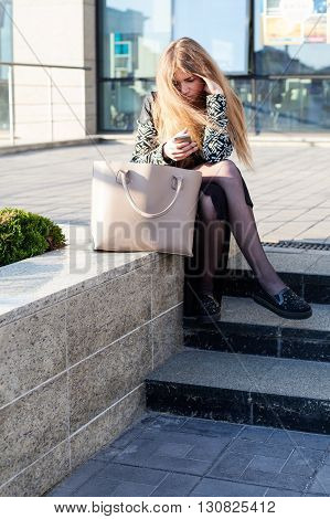 Young woman in a trendy coat is sitting on the stone parapet in the city holding a smartphone looking at the screen