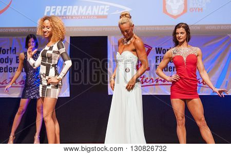 MAASTRICHT THE NETHERLANDS - OCTOBER 25 2015: Female fitness models in evening dress show their best physique in championship on stage at the World Grandprix Bodybuilding and Fitness of the WBBF-WFF