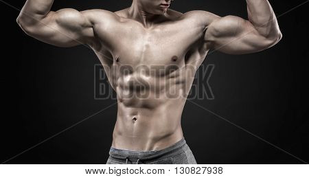 Fitness man model torso posing and showing perfect body, six pack abs, shoulders, biceps, triceps and chest on black background. Close up
