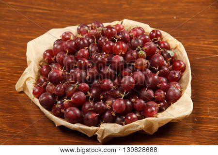 A plate with lots of berries gooseberries on a wodden table