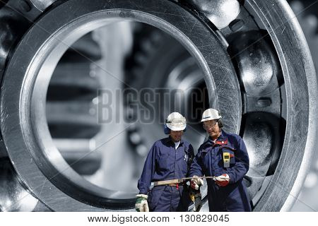 mechanics, engineers with giant steel bearings in background