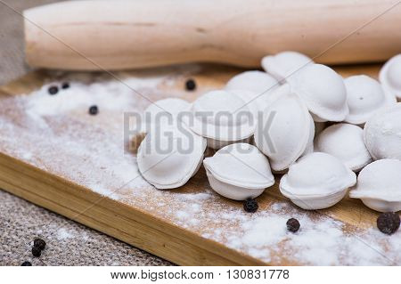 Uncooked dumplings Pelmeni. Traditional Russian dish. Background from russian crude pelmeni laid out on a chopping board