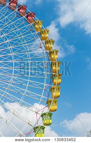 amusement ferris wheel against a blue sky