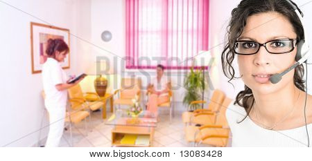 Recepcionista de hospital feminino jovem receber telefonemas no fone de ouvido com sala de espera de clínica em volta