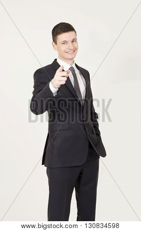 Handsome young business man points finger at you on the gray background.