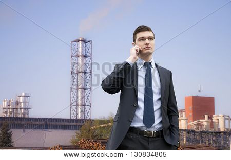 Portrait of an handsome young businessman on the industrial building background with coffe