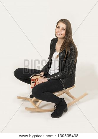 Teenage girl with cute soft toy riding a rocking horse