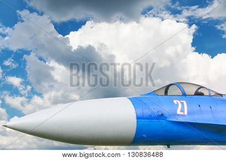 Nose and cabin of the Russian fighter against the blue sky with clouds