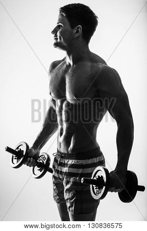 Man showing his six pack abs on dark background