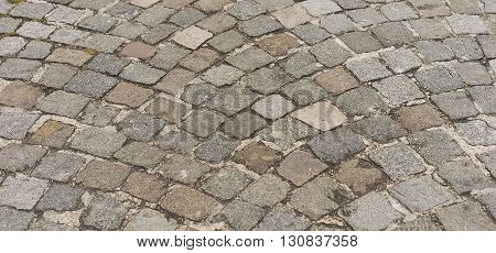 Panorama old traditional european style cobblestone road texture background with granite blocks stones and brickwork pattern