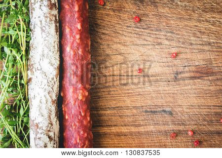 Italian flag made up of red and white salami and green sprigs of thyme on wooden board