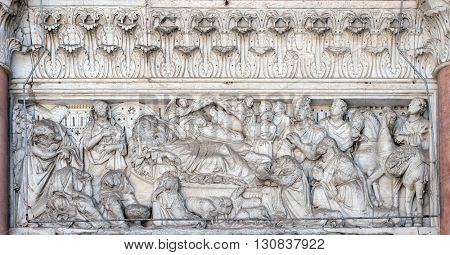 LUCCA, ITALY - JUNE 06, 2015: Annunciation, Nativity and Adoration of the Magi, lunette over the portal of Cathedral of St Martin in Lucca, Italy, on June 06, 2015