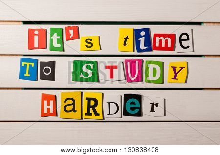 It's time to study harder - written with color magazine letter clippings on wooden board. Concept  image.
