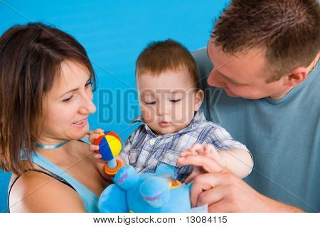 Portrait of happy casual family. Baby boy ( 1 year old ) and young parents father and mother together against blue background, smiling.