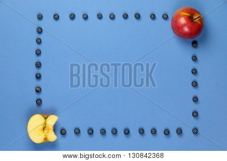 Apple and apple bitten off with frame of blueberries on a blue background. It can be used for advertising of healthy nutrition