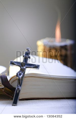 Old Cross and the Holy Bible laying on the table in fornt of a lighting candle.