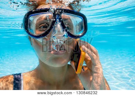 Beautiful girl takes a call to smart phone underwater