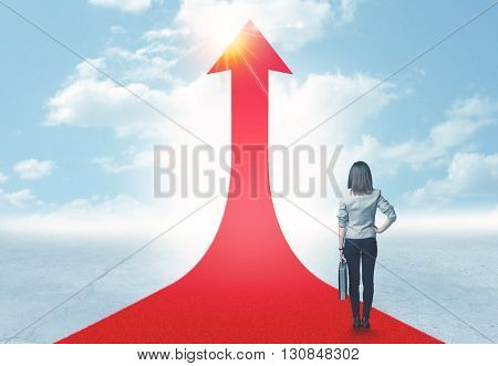 Concept of the road to success with a businesswoman standing on a red arrow