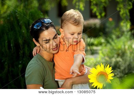 Two years old baby boy and mother enjoy the summer together, playing with a sunflower in the garden. Outdoor, sunlight.