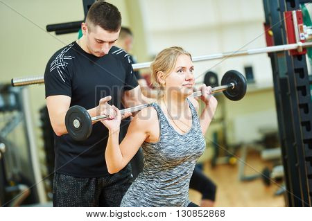 fitness trainer works with woman in gym