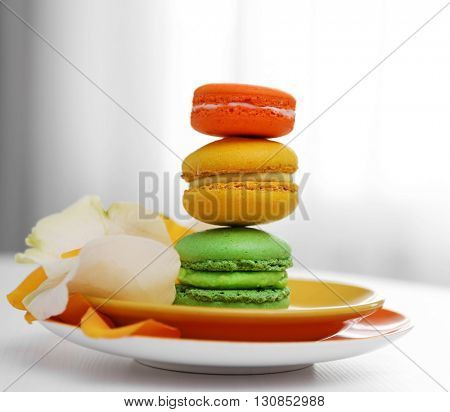 Colorful macaroons on plate on the table indoors