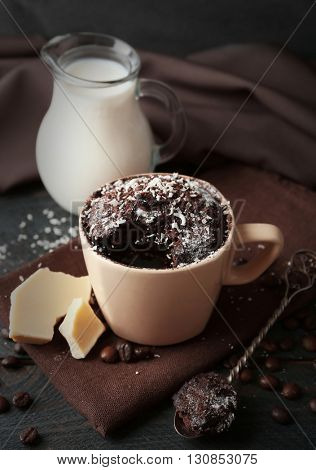 Chocolate fondant cake in cup on wooden table closeup