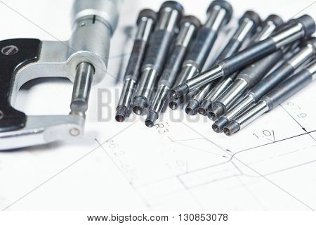 metal part machining. Details with measuring micrometer on print drawing