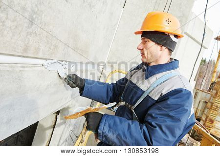 Facade plasterer sealing joint of building wall with putty